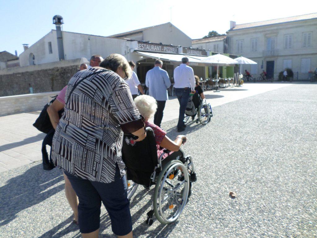 Place Gambetta, un groupe de personnes dont deux en fauteuil roulant, circulent sur la voirie accessible.