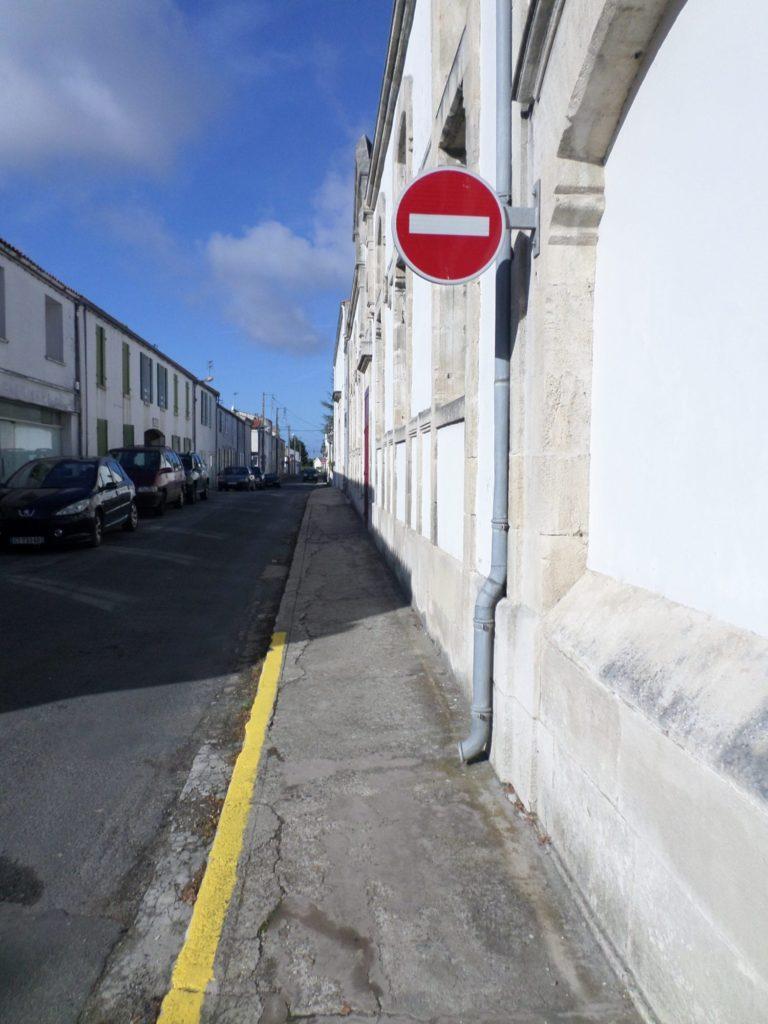 Sur la photo, nous pouvons voir un trottoir non accessible aux personnes en situation de handicap dans le centre-bourg du Château d'Oléron.